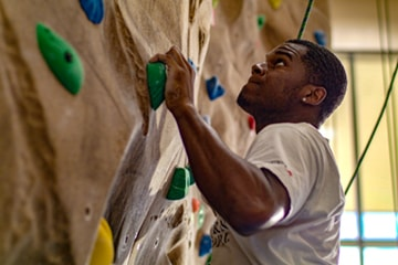 Student on Rock Climbing Wall Inside Payne Center