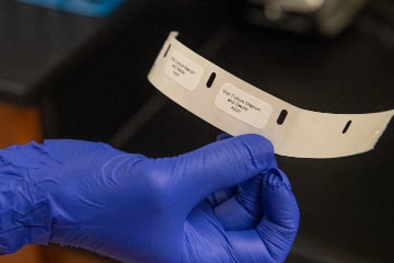 Gloved Hand with Lab Supply Labels