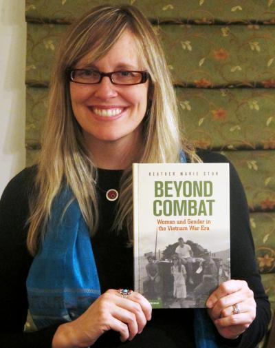 "History professor Dr. Heather Stur with a copy of her new book ""Beyond Combat:"