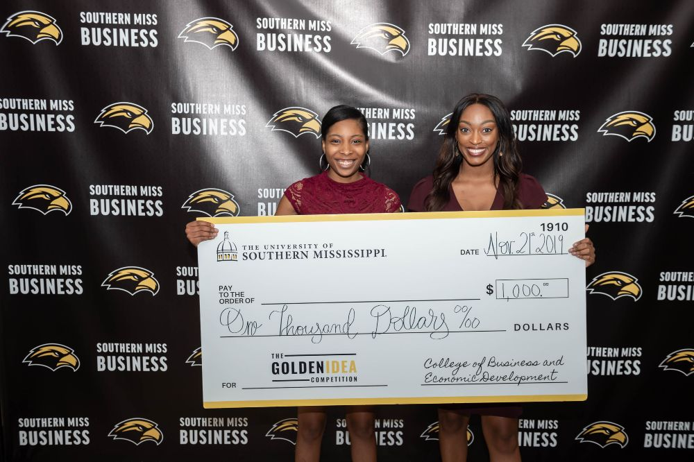 Tiera Bryant and Whitney Jackson pose with their check