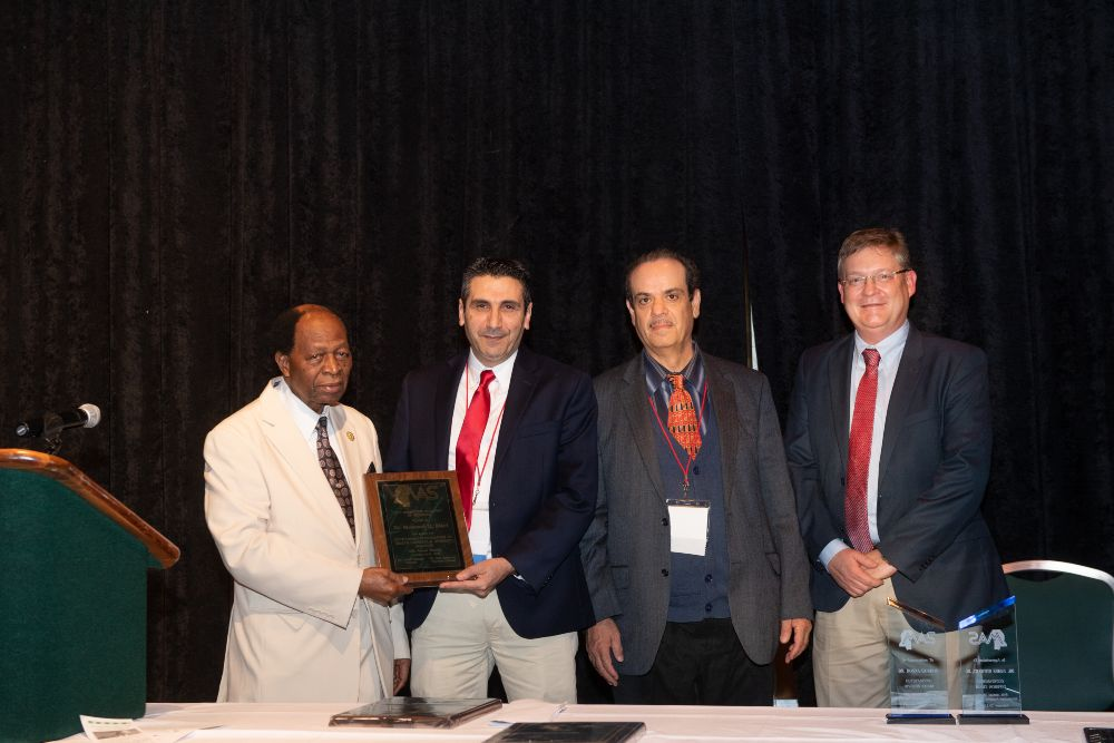 Dr. Mo Elasri, second from left, a professor of microbiology at USM, is presented the Outstanding Contributions to Health Disparity and Diversity Research Award at the Mississippi Academy of Sciences' (MAS) 84th annual meeting, held Feb. 20-21 in Biloxi. Presenting the award to Dr. Elasri is, from left, Dr. Alex Acholonu, chair of the MAS Health Disparities Committee; Dr. Ham Benghuzzi, MAS executive director; and Dr. Ken Butler, chair of the Awards Committee of MAS.