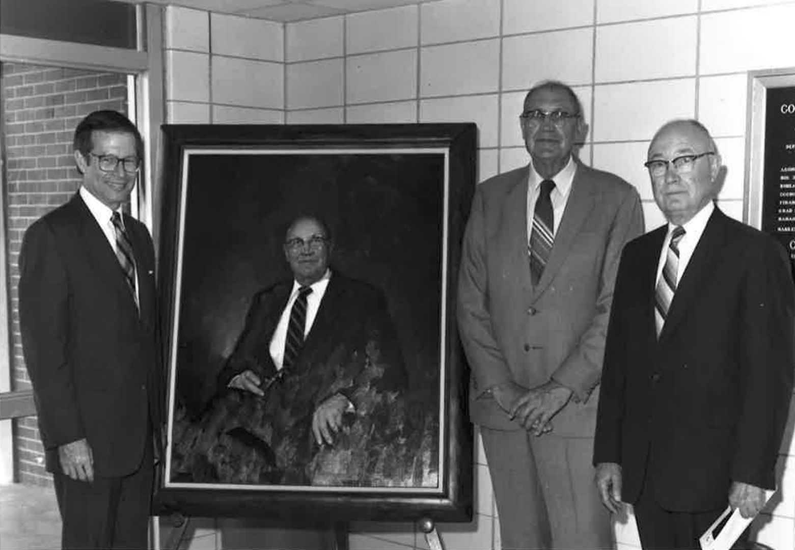Men pictured with portrait of Dr. Joseph Greene