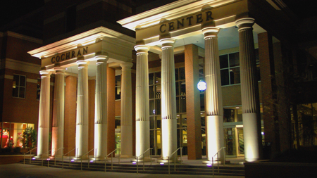 Exterior photo of front of Thad Cochran Center at night.