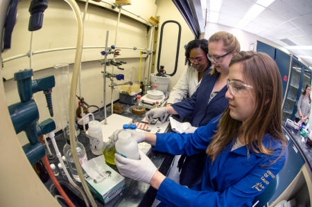 Graduate and undergraduate students work in fume hood